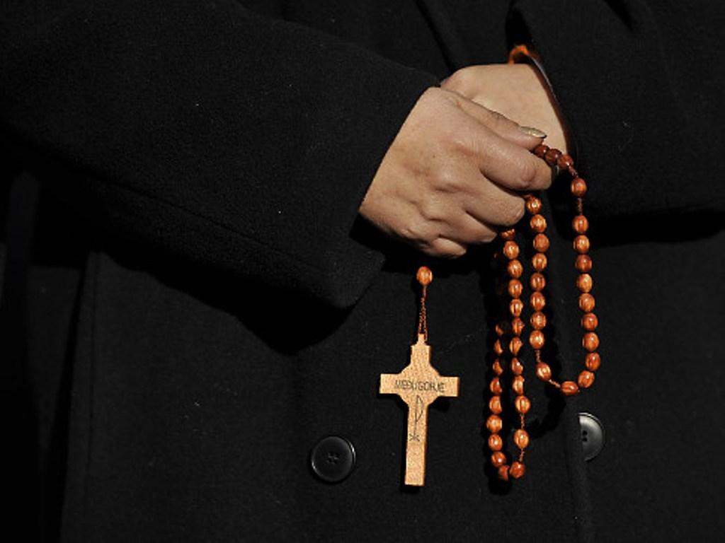 крест в руке священника